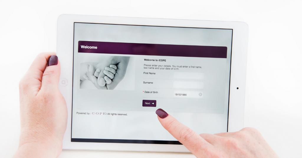 A woman holding an iPad using iCOPE screening